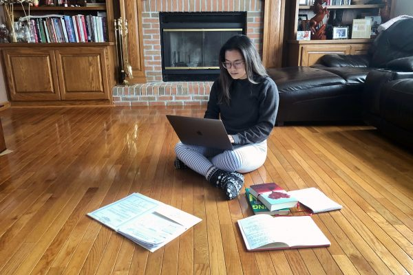 Kayla Huynh studying on the floor of her family room at home.